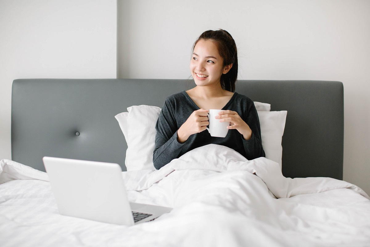 woman drinking something in bed