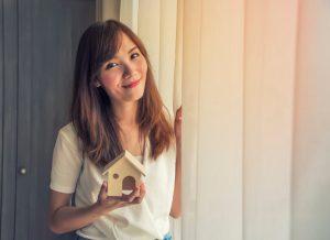holding a miniature house