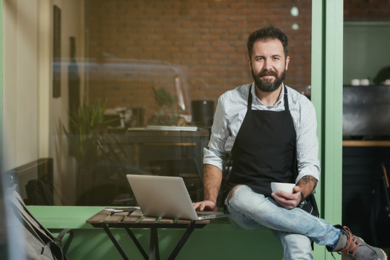 barista holding a cup and laptop